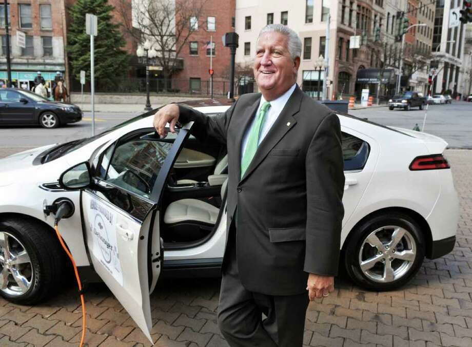 Albany Mayor Jerry Jennings with a Chevy Volt electric car during a news conference at SUNY Plaza in Albany Thursday morning April 21, 2011. In recognition of Earth Day, Mayor Jennings announced a multi-stakeholder partnership to identify opportunities and challenges to preparing Albany for the electric vehicle.  (John Carl D'Annibale / Times Union) Photo: John Carl D'Annibale / 00012862A