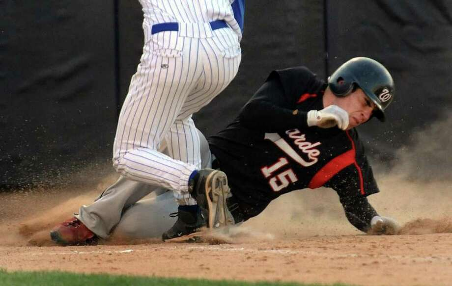 Fairfield Warde's #15 Will Halliday slides into home plate to score a run, during boys baseball action against Fairfield Ludlowe at the Ballpark at Harbor Yard in Bridgeport, Conn. on Thursday April 21, 2011. Looking to make the tag is Ludlowe's pitcher #6 Victor D'Ascenzo. Photo: Christian Abraham / Connecticut Post