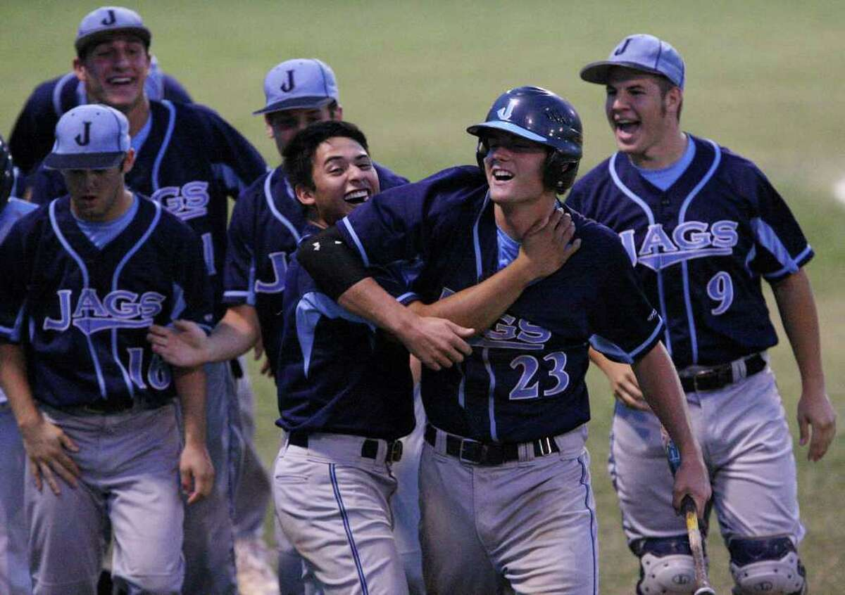FOR SPORTS - Johnson's Klaus Bohrmann (center right) celebrates with teammate Marcus Cardoza after scoring against Reagan in the second inning Thursday April 21, 2011 at Blossom baseball field. (PHOTO BY EDWARD A. ORNELAS/eaornelas@express-news.net)