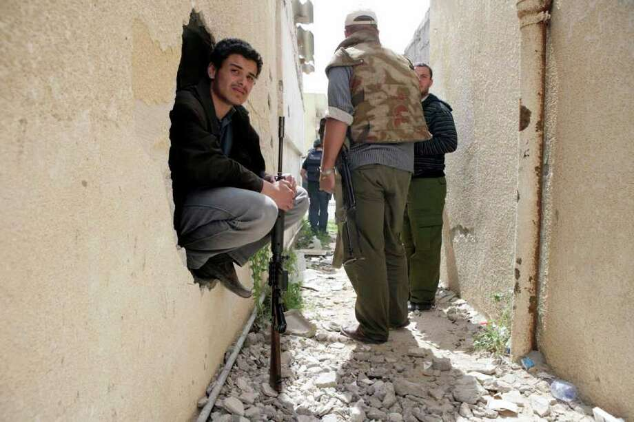 Libyan rebel fighters take cover in an alley while battling pro-Gadhafi troops in the besieged city of Misrata, the main rebel holdout in Gadhafi's territory, Thursday, April 21, 2011. (AP Photo) Photo: STR / AP