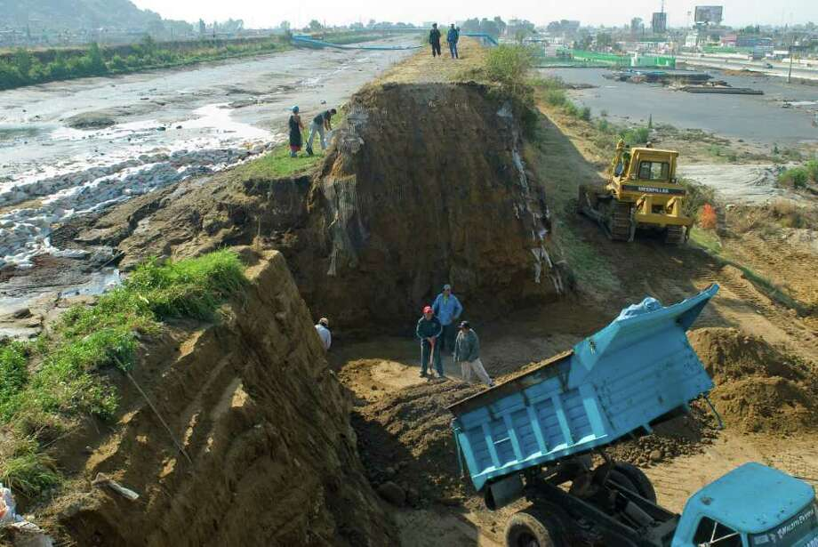 Workers shore up a levee that was built to contain the sewage and rainwater of the Compania canal in Valle de Chalco, Mexico. Photo: Keith Dannemiller/Houston Chronicle / Freelance