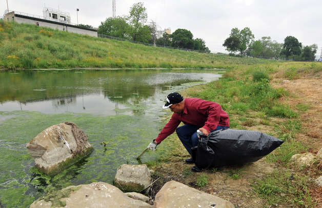 Brian Rawls cleans up trash along the San Antonio River near Roosevelt Park as part of the Armed Forces Earth Day campaign on Tuesday, April 19, 2011. The site south of downtown was chosen for the cleanup because litter from Fiesta revelry tends to collect there. Photo: Robin Jerstad/Special To The Express-News