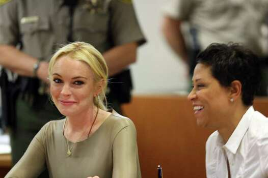 Lindsay Lohan, left, smiles with her attorney, Shawn Chapman Holley at Los Angeles Superior Court, Thursday, March 10, 2011. Lohan has rejected a plea agreement offered by prosecutors that included a guaranteed return to jail. She told a judge she agreed to delaying her case until a preliminary hearing when prosecutors will present evidence against her Photo: AP