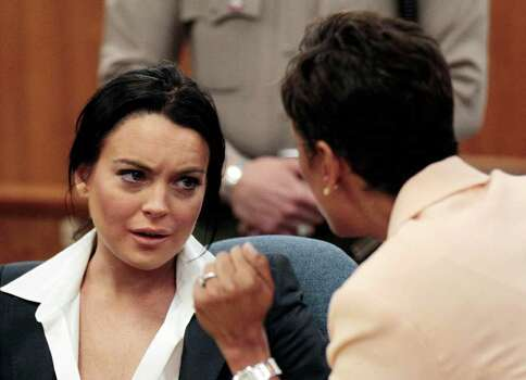 Actress Lindsay Lohan, left, talks to her attorney Shawn Chapman Holley during a hearing in Beverly Hills, Calif., Monday, May 24, 2010. Photo: AP