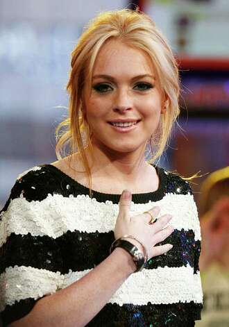 "Actress Lindsay Lohan appears on stage during a taping of  MTV's ""Total Request Live"" show in this May 8, 2007, file photo in New York. Lindsay Lohan's legal problems continue even while she recovers in rehab. The 20-year-old starlet has been sued by Grandeur Inc., which claims the actress crashed into a company van in October 2005. Photo: Jeff Christensen, AP / AP"