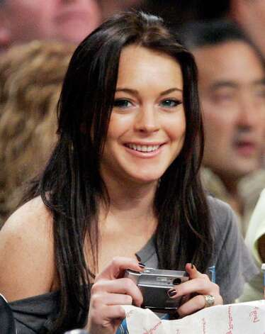 "**FILE**Actress Lindsay Lohan smiles at the camera as she watches the Los Angeles Lakers play the Atlanta Hawks in an NBA basketball game, last Friday night, Dec. 8, 2006, in Los Angeles. Lohan says she's been going to Alcoholics Anonymous meeting for a year, but hasn't talked about it because it's ""no one's business.""  ""I haven't had a drink in seven days. Or anything,""  the 20-year-old actress tells People magazine in a story posted Tuesday, Dec. 11, 2006, on its Web site. Photo: MARK J. TERRILL, AP / AP"