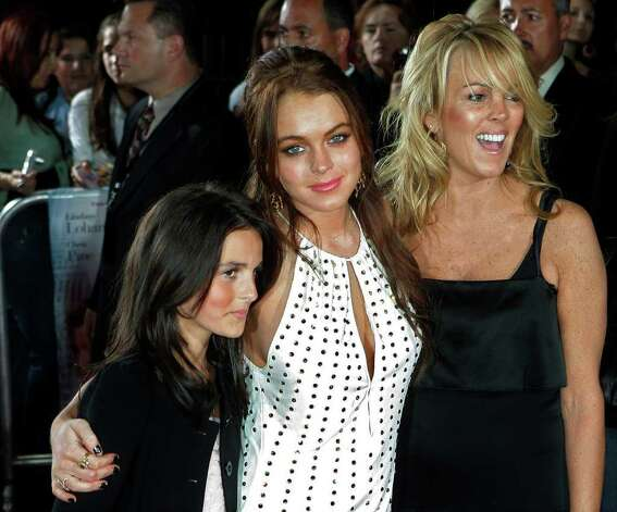 "**FILE** Actress Lindsay Lohan poses with her mother Dina, right, and her sister Aliana after they arrived to the premiere of her new film ""Just My Luck'""  in this file  photo from May 9, 2006, in Los Angeles. A studio executive was ""way out of line"" for scolding Lindsay Lohan for her absences from the set of her new movie, Lohan's mother Dina tells ""Access Hollywood"" in an interview set to air Monday. Photo: KEVORK DJANSEZIAN, AP / AP"
