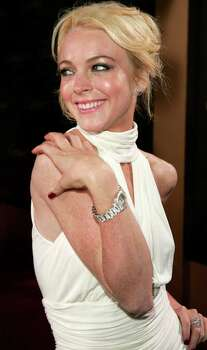 "**FILE**Lindsay Lohan arrives for a benefit on May 9, 2005 in Beverly Hills, Calif. Lohan missed her own premiere in London Thursday, July 28, 2005, to fly home to her mother for the start of her parents' divorce proceedings. Lohan was meant to join her co-star Michael Keaton at the premiere of the Disney film ""Herbie: Fully Loaded."" Photo: CHRIS POLK, AP / AP"
