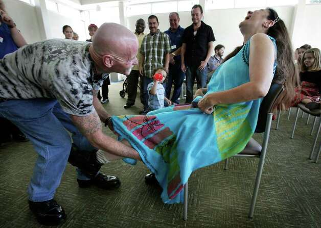 Haven for Hope resident Brenda Willborn, right, laughs as her new husband Marion Wright, also a resident at the shelter, reaches for her garter belt, following their wedding at the Chapel of Hope at Haven, Saturday, Dec. 4, 2010.  Photo: BOB OWEN, SAN ANTONIO EXPRESS-NEWS / SAN ANTONIO EXPRESS-NEWS