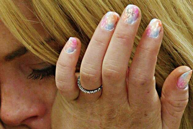 Lindsay Lohan cries as she is sentenced to 90 days jail by Judge Marsha Revel during her hearing at the Beverly Hills Courthouse on July 6, 2010. The star had apparently painted the nail of her middle finger with the words 'Fuck U'. Troubled Hollywood starlet Lindsay Lohan broke down in tears after she was sentenced to 90 days in jail for violating her probation in two 2007 drunk driving cases. The actress, once a red-headed Disney films star and promising A-lister whose career since has spun off course, also was ordered to participate in a 90-day inpatient substance abuse program. After Beverly Hills Superior Court Judge Marsha Revel sentenced Lohan, 24, the actress and fashion muse wept in court.               AFP PHOTO/POOL/David McNew Photo: DAVID MCNEW, AFP/Getty Images / 2010 AFP