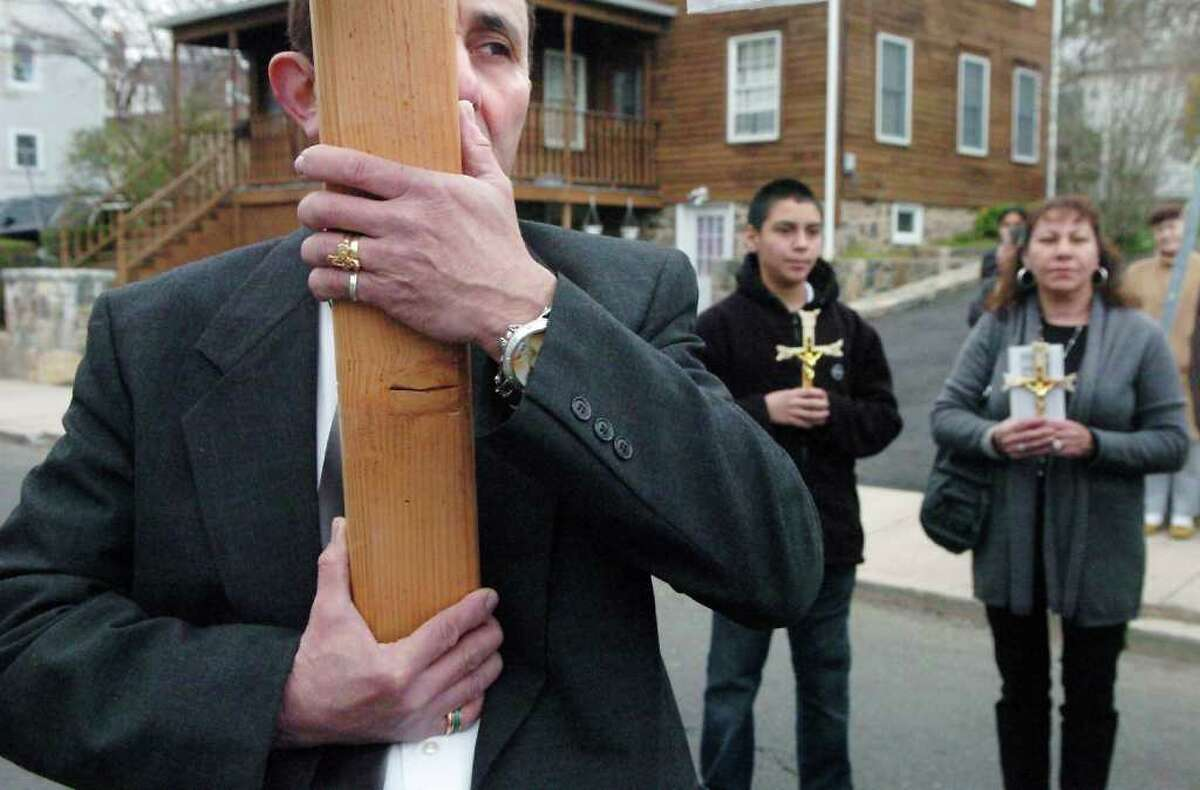 Ramero Otalvaro holds a cross as Jason Munoz and Maria Garcia join the procession during the Stations of the Cross from Cummings Park to St. Benedict-Our Lady of Montserrat Church on Good Friday in Stamford, Conn. on Friday April 22, 2011.