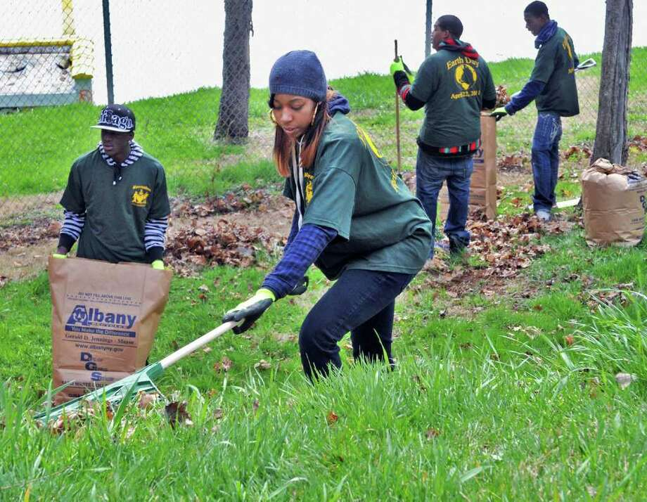 Ahraea Permaul, 19, center, and other participants in Albany Youth Build  mark Earth Day by cleaning up winter debris in Albany's Lincoln Park Friday morning April 22, 2011. Youth Build is an organization that gives young people a second chance at earning high school diplomas and helps in job placement. It is funded by the U.S. Department of Labor and works in partnership with the Albany Housing Authority.  (John Carl D'Annibale / Times Union) Photo: John Carl D'Annibale / 00012850A