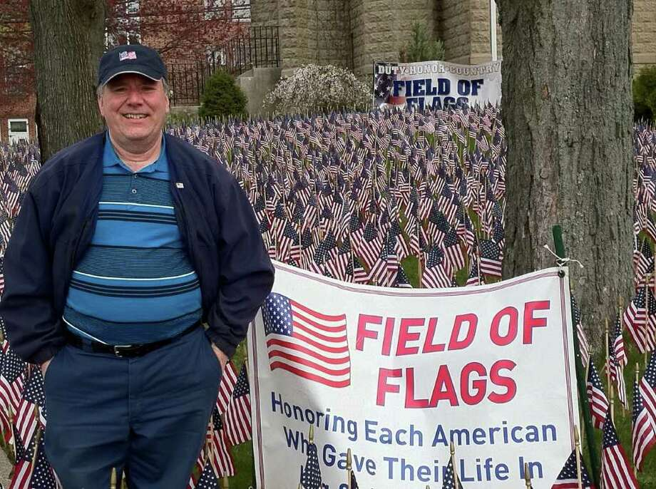 Norwalker Paul Mordoff stands in front of the Field of Flags memorial at Christ Episcopal Church in East Norwalk following a dedication ceremony Friday morning. He was instrumental in bringing the memorial to the city. Each flag represents an American casualty in Iraq and Afghanistan. The 5,984 flags will be on display for three weeks before moving on to Danbury. Photo: Photo By Nicole Rivard, Contributed Photo / Norwalk Citizen