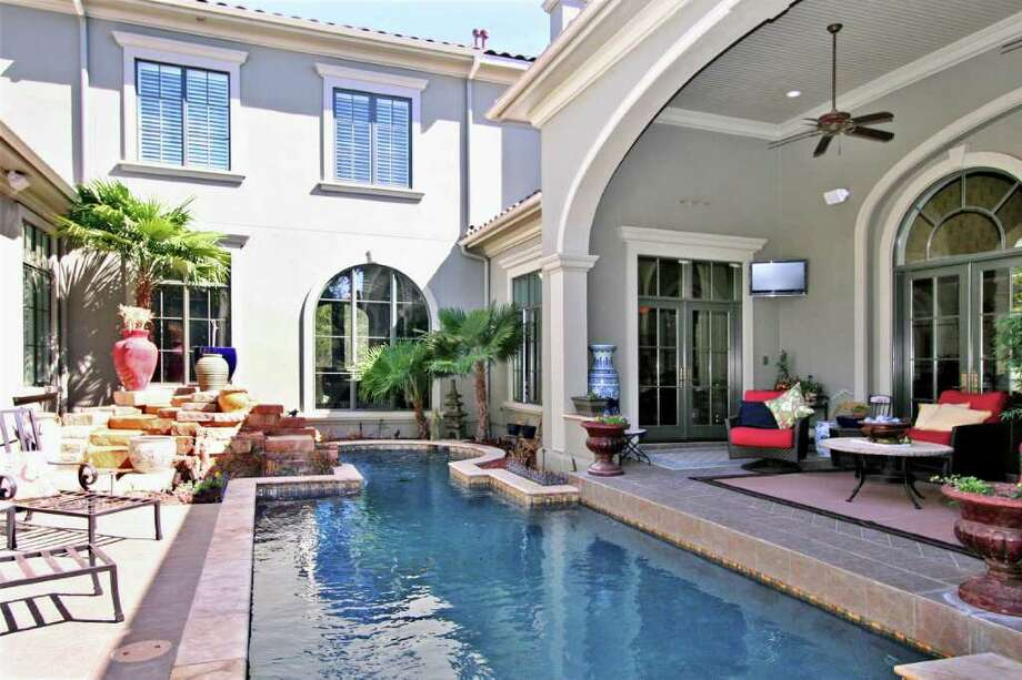 A big, covered patio and lots of windows make the swimming pool of this outdoor space a focal point of this four-bedroom, six-bathroom house. The 6,213-square-foot home has a list price of $2,490,000. Photo: COURTESY PHOTO / COURTESY OF THE PHYLLIS BROWNING CO.