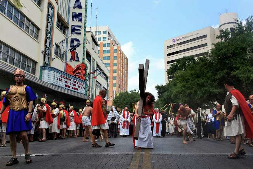 Jesus, played by Bruno Horwath, carries the Cross on Houston Street from Milam Park to San Fernando Cathedral during the Passion Play on Friday, April 22, 2011. LISA KRANTZ/lkrantz@express-news.net