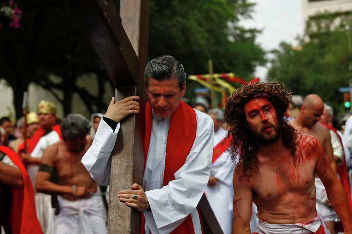 San Antonio Archbishop Gustavo Garcia-Siller takes his turn carrying the cross as he walks with Bruno Horwath, right, as Jesus, during the Passion Play on Friday, April 22, 2011. LISA KRANTZ/lkrantz@express-news.net