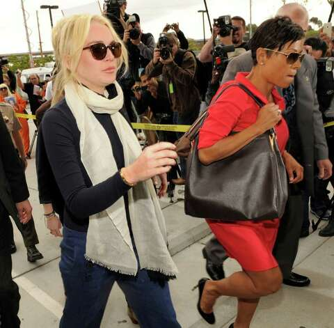 Lindsay Lohan, left, arrives with her lawyer, Shawn Chapman Holley for a preliminary hearing, Friday, April 22, 2011, at LAX Courthouse in Los Angeles. Lohan is in court for a hearing on a felony grand theft charge involving a necklace reported stolen by an upscale jewelry store. (AP Photo/Chris Pizzello) Photo: Chris Pizzello