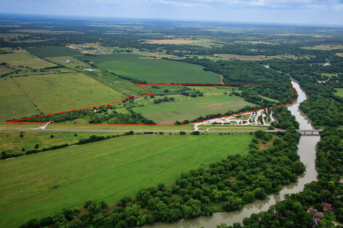 The red line delineates the borders of an 86.2-acre site in Guadalupe County along the Guadalupe River listed at $3.6 million. The property includes two houses and a barn.