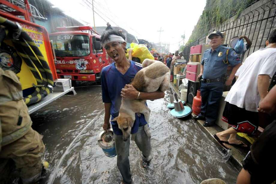 A resident carries his pet dog as fire rages through informal settlers' homes in the Makati financial district of Manila on April 19, 2011. The fire razed a sprawling residential compound in the Philippine capital's financial district, leaving up to 10,000 people homeless, authorities said. Photo: AFP/Getty Images