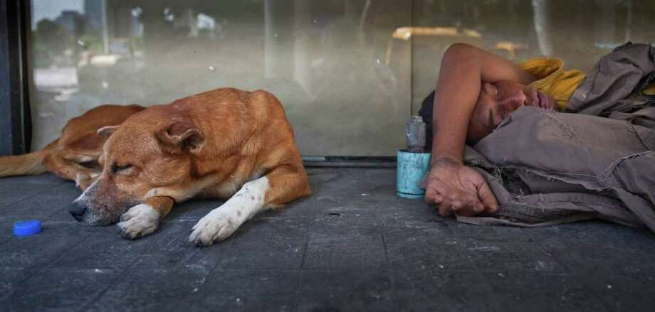 A Thai New Year reveler and dog sleep near Silom Ave. in downtown Bangkok Saturday, April 16, 2011.  Silom Ave., which is part of Bangkok's business and finance district, has become the scene of rowdy, crowded Thai New Year celebrations for the past few years. Photo: AP