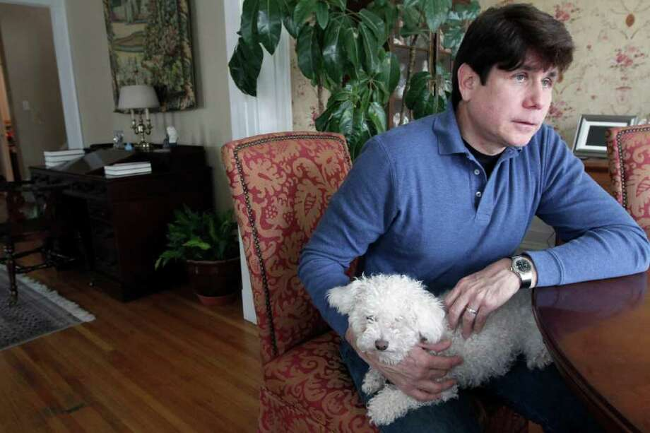 Former Illinois Gov. Rod Blagojevich holds the family dog Skittles as he speaks about his upcoming retrial on April 16, 2011 at his home in Chicago. Blagojevich who was convicted of one count of lying to the FBI in his original trial, faces 20 federal counts at his second trial, including allegations that he tried to sell or trade President Barack Obama's former Senate seat. Photo: AP