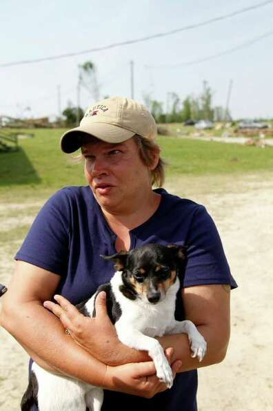 Kimberly Smith holds her dog Spot as she stands in outside her destroyed home in Askewville, N.C., T