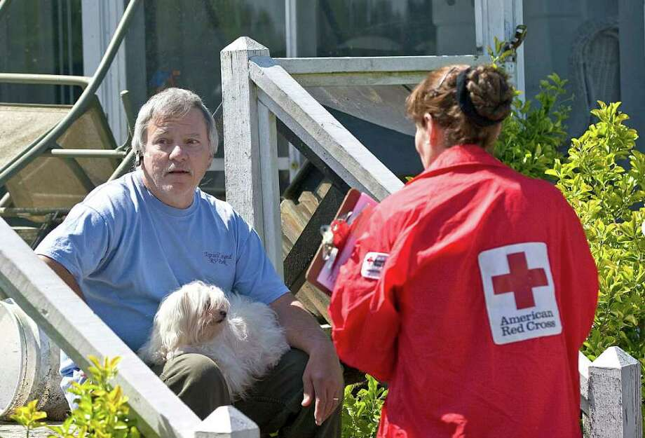 Tornado victim Clay Anderson, left, with his dog Mindy, sits on the steps of his back porch and talks with American Red Cross volunteer Kathi Garrett on Sunday, April 17, 2011 in the Saint Andrews community in Sanford, N.C. Photo: AP
