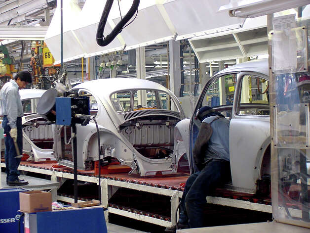 "Brand-new ""old"" Beetles roll down the assembly line in Puebla, Mexico, in July 2001. Production of these early design, rear-engine models ended in 2003; they were sold only in Mexico, as U.S. sales had been discontinued in 1979. Photo: G. CHAMBERS WILLIAMS III/SPECIAL TO THE EXPRESS-NEWS"