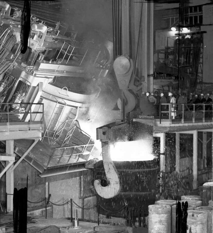 The March 7, 1958 photo caption read: One hundered tons of whtie hot steel pours from the spout of the new electric furnace which Bethlehem Pacific Coast Steel put into operation this week at its Seattle plant. Note the size of the men on the platform right center. Furnace is biggest in the West. Photo: Seattlepi.com File