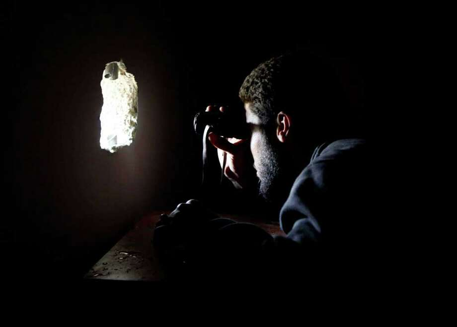 A Libyan rebel fighter uses a scope to peek through a hole in a wall during a battle with pro-Gadhafi troops in the besieged city of Misrata, the main rebel holdout in Gadhafi's territory, Friday, April 22, 2011. (AP Photo) / AP
