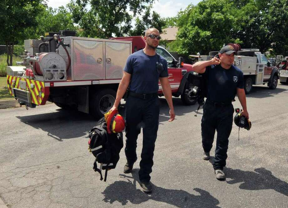 New Braunfels firefighter Jason Wallace (left) and Ruben Lopez of the Bulverde Fire Department carry gear into the San Antonio Fire Department's station #40 after returning 4/22 from 9 days of fighting the Possum Kingdom wildfire in north Texas. Photo: Robin Jerstad/Special To The Express-News / Copyright 2011 by Robin Jerstad 210-254-6552