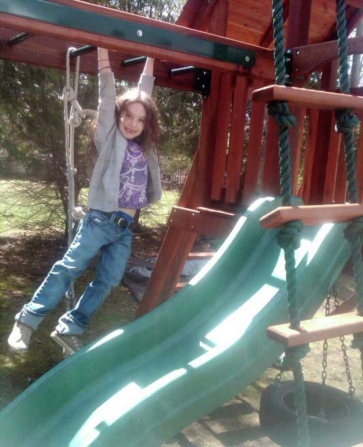 Lynnea Moskowitz, daughter of Cary Moskowitz, hangs out on the monkey bars of her swing set. Photo: Contributed Photo / Westport News contributed