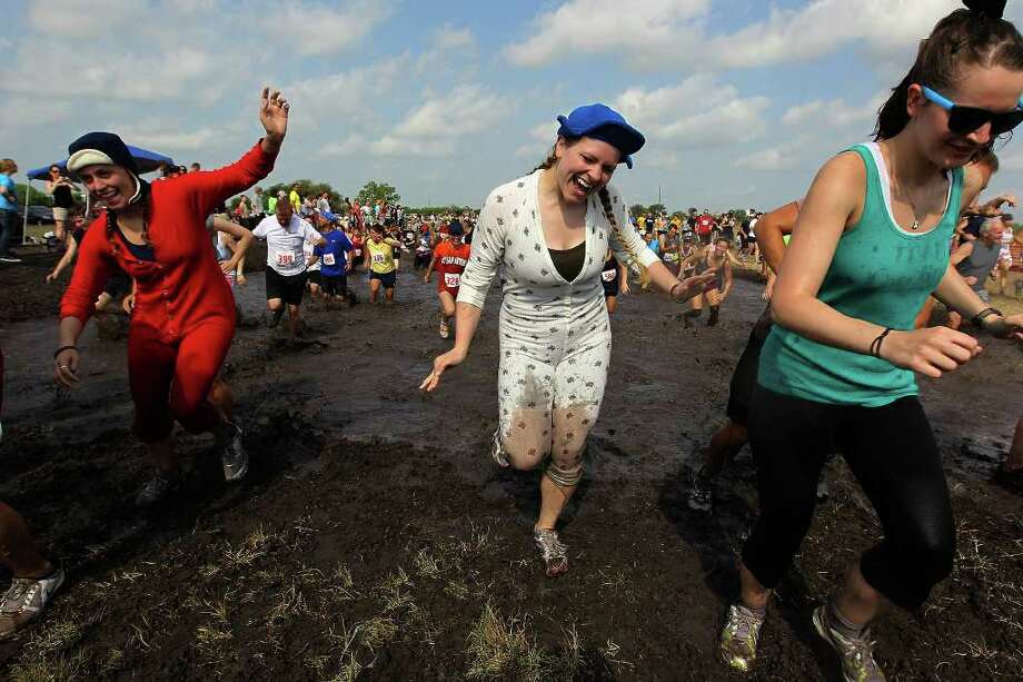 Elise Heck (center) and Caitlin Scarborough (left) join other runners in the Muddy Mayhem 8K run sponsored by The Athlete's Foot on Saturday, April 23, 2011. Runners dealt with several obstacles including a giant, muddy water hole near the finish. Over 1,000 runners participated in the fun yet mucky mess. Proceeds went to Wounded Warrior Project. Photo: KIN MAN HUI, Kin Man Hui/kmhui@express-news.net / San Antonio Express-News