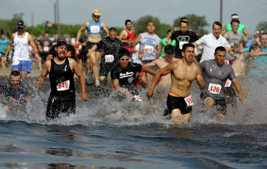 Runners head straight for the massive water hole at the start of the race.