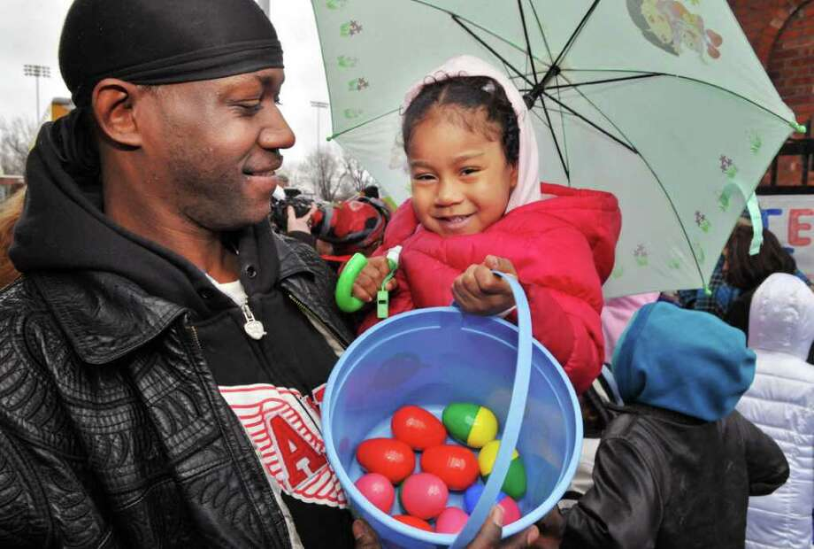 Antonio Watson of Albany and his 3-year-old daughter Ava Watson show off a basket of Easter eggs handed out at Bleeker Stadium in Albany Saturday April 23, 2011.  The originally planned Easter egg hunt was postponed due to the rain and cold.  (John Carl D'Annibale / Times Union) Photo: John Carl D'Annibale / 00012861A