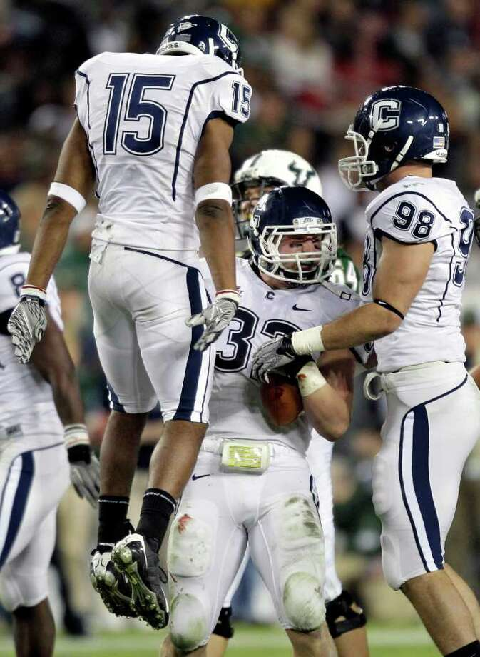Connecticut linebacker Scott Lutrus (32) celebrates with teammates Jerome Junior (15) and Ted Jennings (98) after intercepting a South Florida pass during the first quarter of an NCAA college football game Saturday, Dec. 4, 2010, in Tampa, Fla. (AP Photo/Chris O'Meara) Photo: AP