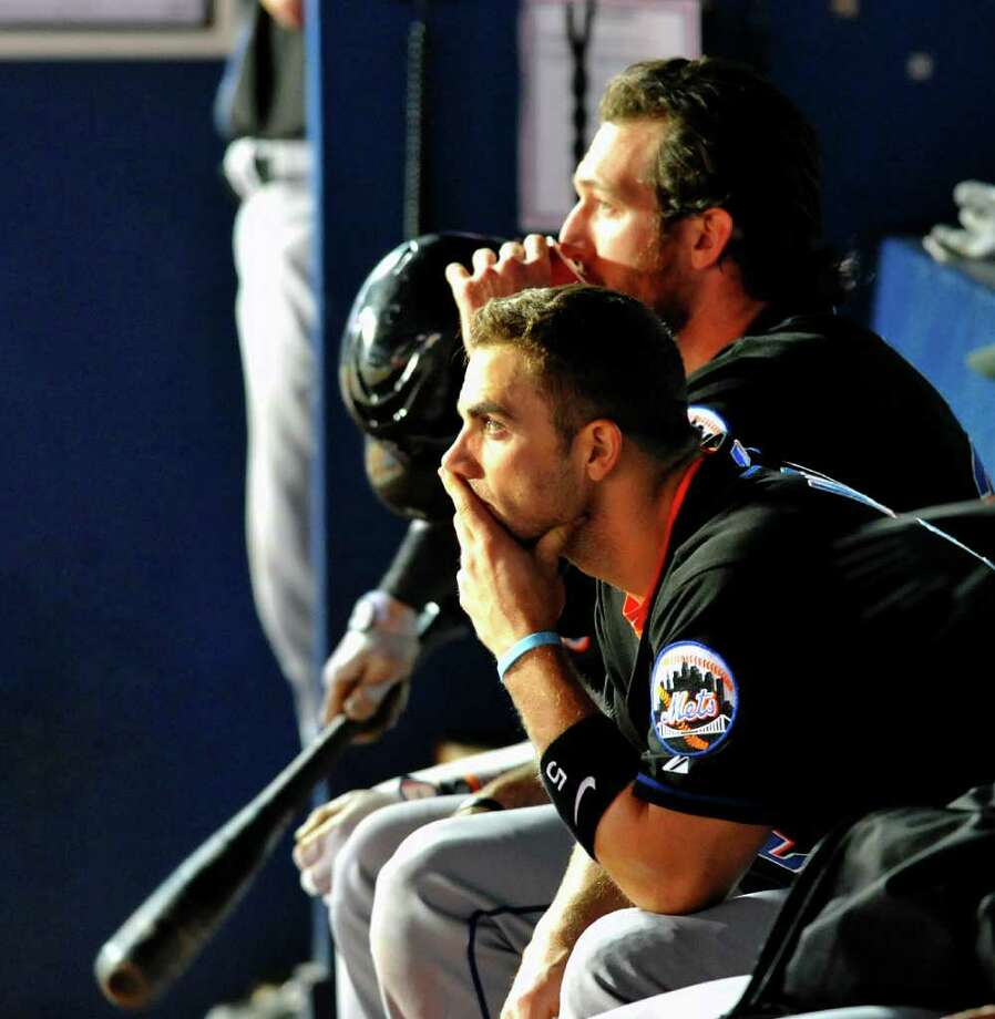 New York Mets David Wright, right, sits in the dugout with \New York Mets Ike Davis, rear, as they watch their team bat against the Atlanta Braves during the ninth inning, in the second baseball game of a doubleheader  Saturday, April 16, 2011, at Turner Field in Atlanta. The Braves went on to win 4-0. (AP Photo/Gregory Smith) Photo: AP