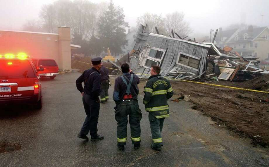 A group of fire fighters from the Bridgeport Fire Department arrive to inspect the demolition site next to the Masjid An-Noor Mosque along Fairfield Avenue in Bridgeport, Conn. on Saturday April 23, 2011. Photo: Christian Abraham / Connecticut Post