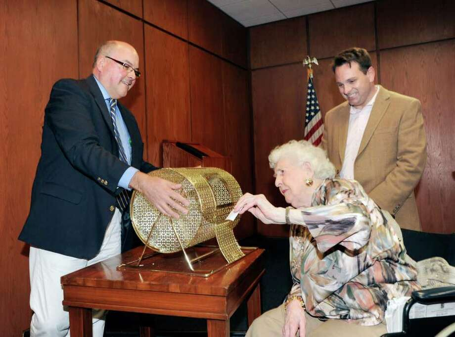 "Nathaniel Witherell nursing home resident Helen Weisner draws the winning raffle ticket on behalf of the Greenwich Police Silver Shield Association during Regis Philbin Day at Greenwich Town Hall, Friday afternoon, April 15, 2011. The prize was four VIP tickets to the ABC television show ""Live! With Regis and Kelly."" At left is Scott Neff, director of The Friends of Nathaniel Witherell, and at right is Greenwich Selectman Drew Marzullo. Photo: File Photo / Greenwich Time File Photo"