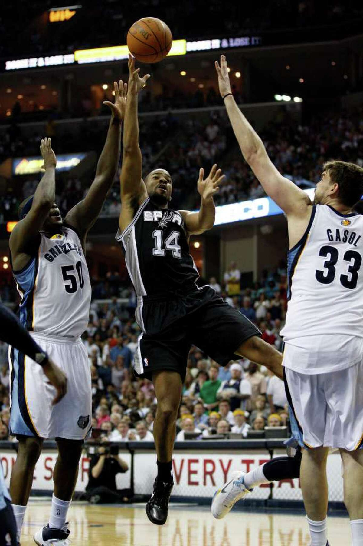 SPURS -- San Antonio Spurs Gary Neal shoots over Memphis Grizzlies Marc Gasol and Zach Randolph during the second half in the third game of the Western Conference Quarter First Round at FedExForum in Memphis, TN, April 23, 2011. The Grizzlies won 91-88 and go up 2-1 in the series. JERRY LARA/glara@express-news.net