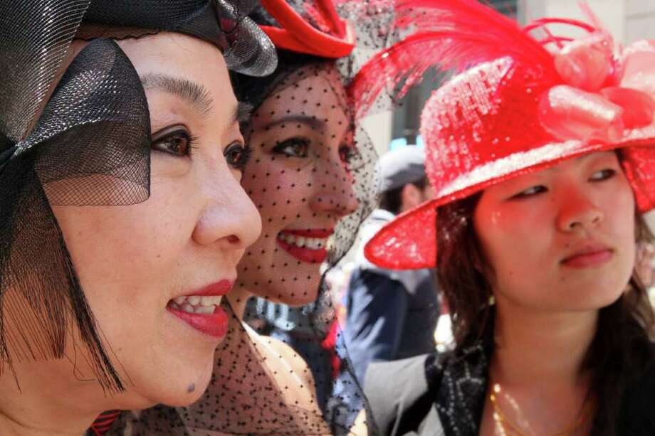 Marjorie Lee Woo, left, Sabrina Mashburn, center, and Ashley Woo, Marjorie's daughter, pose for photographers as they take part in the Easter Parade along New York's Fifth Avenue Sunday April 24, 2011.  Marjorie Lee Woo made the hats.  (AP Photo/Tina Fineberg) Photo: Tina Fineberg