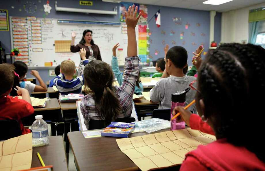 Students raise their hands to answer a question in Elizbeth Moore's second grade class at Julie Newton Aue Elementary School. Class sizes in the district will most likely increase. Photo Bob Owen/rowen@express-news.net Photo: BOB OWEN, Bob Owen/Express-News / rowen@express-news.net