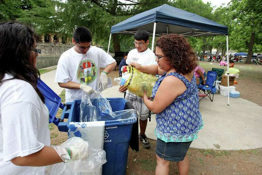 Vivian Hernandez, 12, (from left) and her brother Matthew Hernandez, 14,  collect cans and bottles from Arthur Owens Jr. , 17, and his mother LeiAnn Owens for recycling Sunday April 24, 2011 at Brackenridge Park. Photo: EDWARD A. ORNELAS, Edward A. Ornelas/Express-News / SAN ANTONIO EXPRESS-NEWS (NFS)