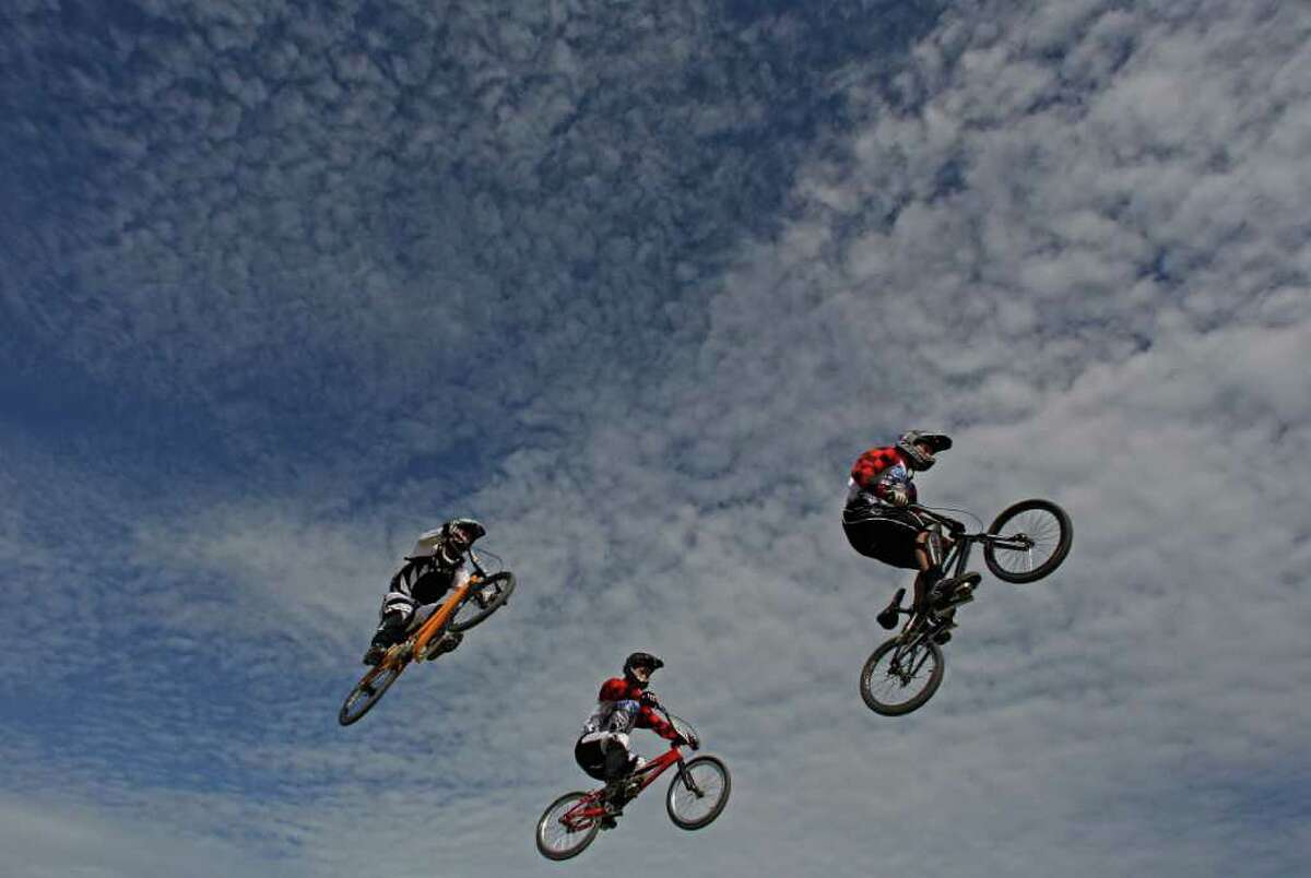 AUCKLAND, NEW ZEALAND - APRIL 23: (L-R) Kurt James of Cambridge, Adam Coker of East City and Kurt Bagby of East City clear a jump in the Elite Men during the New Zealand National BMX Championships held at the North Harbour BMX track on April 23, 2011 in Auckland, New Zealand. (Photo by Phil Walter/Getty Images) *** Local Caption *** Kurt James;Adam Coker;Kurt Bagby;