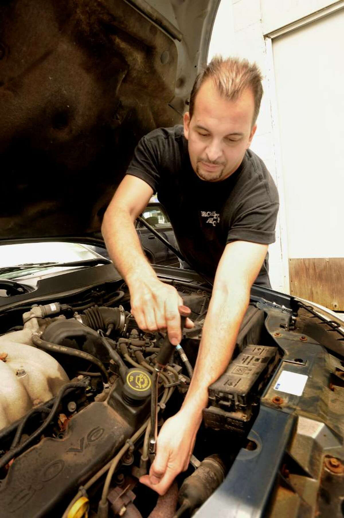 Robert Picqarelli Jr. works on an engine at his New Milford business, Robert's Auto, on Wednesday, Sept.16,2009.