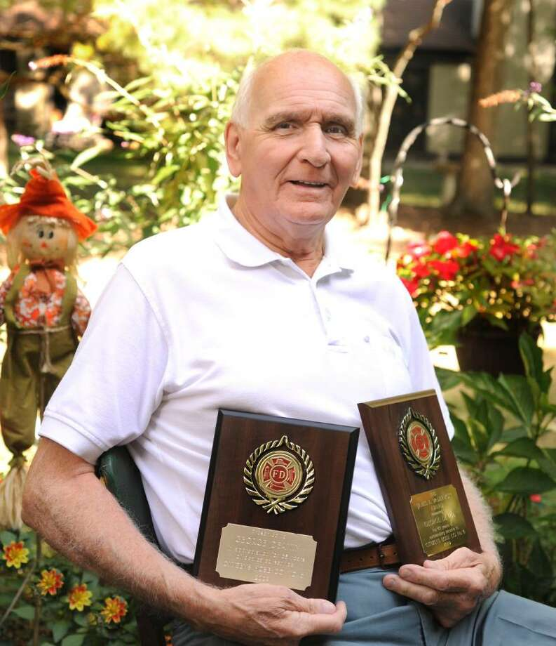 George Deakin, 80, of Southbury, displays two of the awards he recently received from the Citizens Hose Company No. 6 in Danbury. Photographed in Southbury on Friday, Sept. 25, 2009. Photo: Michael Duffy / The News-Times