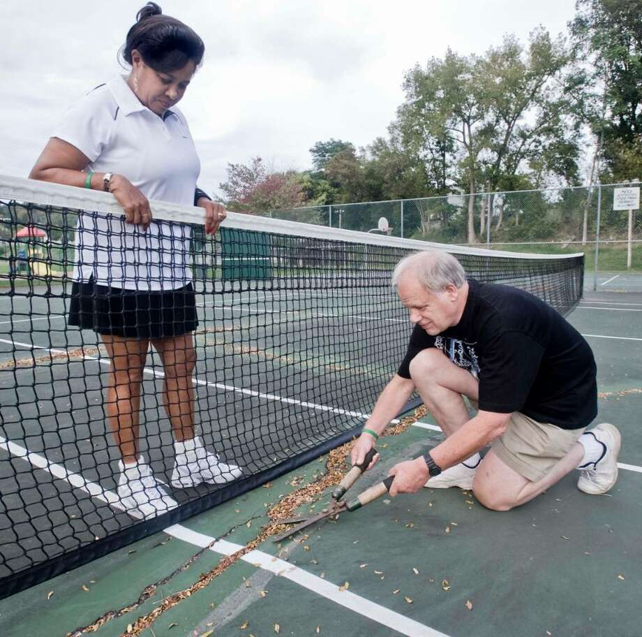 Virginia Payne watches her husband Nicholas trim the weeds growing from the surface cracks at the tennis courts on Young's Field Road, New Milford. Thursday, Sept. 24, 2009 Photo: Scott Mullin / The News-Times