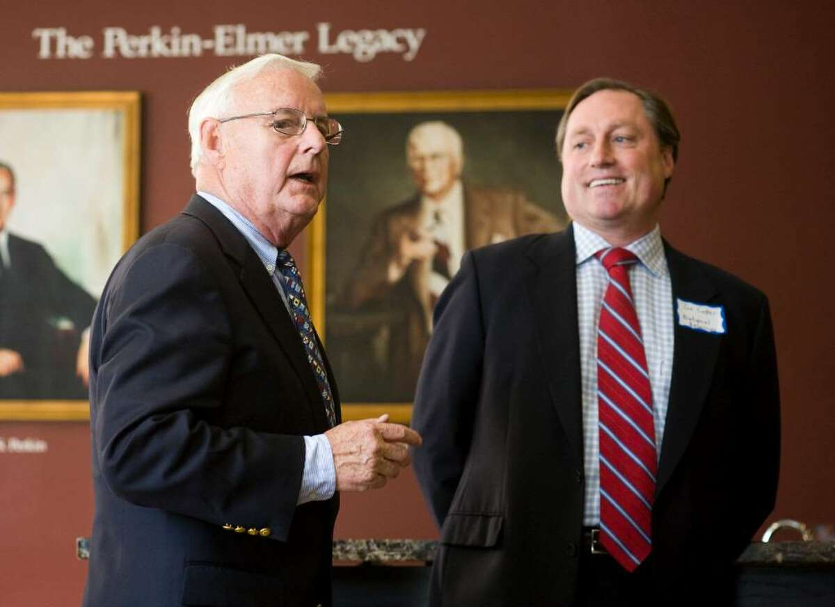 Gaynor Kelley, CEO of Perkin Elmer from 1990 to 1995, left, talks during a dedication ceremony for its new Legacy Room, dedicated to employees of the company. At right is Joe Cotter, a principal for National Resources.