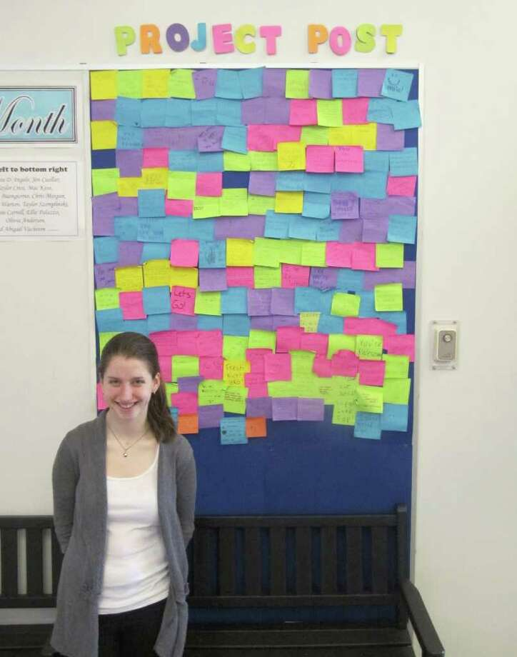 """Melissa Warten,a junior at Fairfield University, stands in front of """"Project POST,"""" located in the high school's lobby. Back on April 11, students were encouraged to write nice things about people without signing their name or naming names. The hope is promote tolerance and acceptance in the high school setting. Photo: Kirk Lang / Fairfield Citizen"""