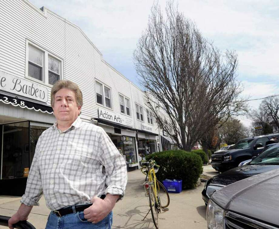Richard Zimmerman owner of Action Arts at 242 Sound Beach Ave., Old Greenwich, stands near a tree which he says obscures his business and is a nesting place for starlings that create a mess in front of his store and along Sound Beach Avenue, Thursday afternoon, April 14, 2011. The Greenwich tree warden ruled Monday against removing the tree and seven others from the avenue. Photo: Bob Luckey, ST / Greenwich Time